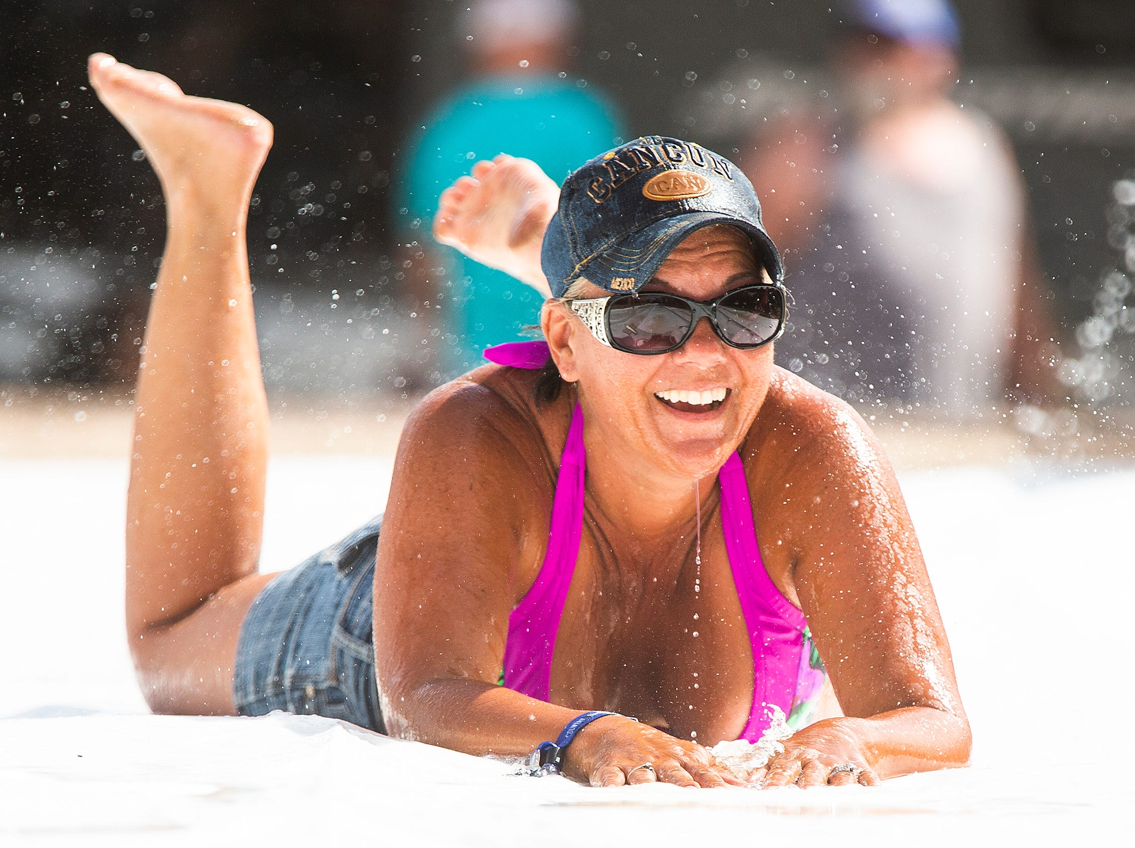 Cindy Packer, 43, Surprise, does the slip and slide at Camp Crazy Coyote at the Country Thunder Arizona 2019 music festival outside Florence, Thursday, April 11, 2019.
