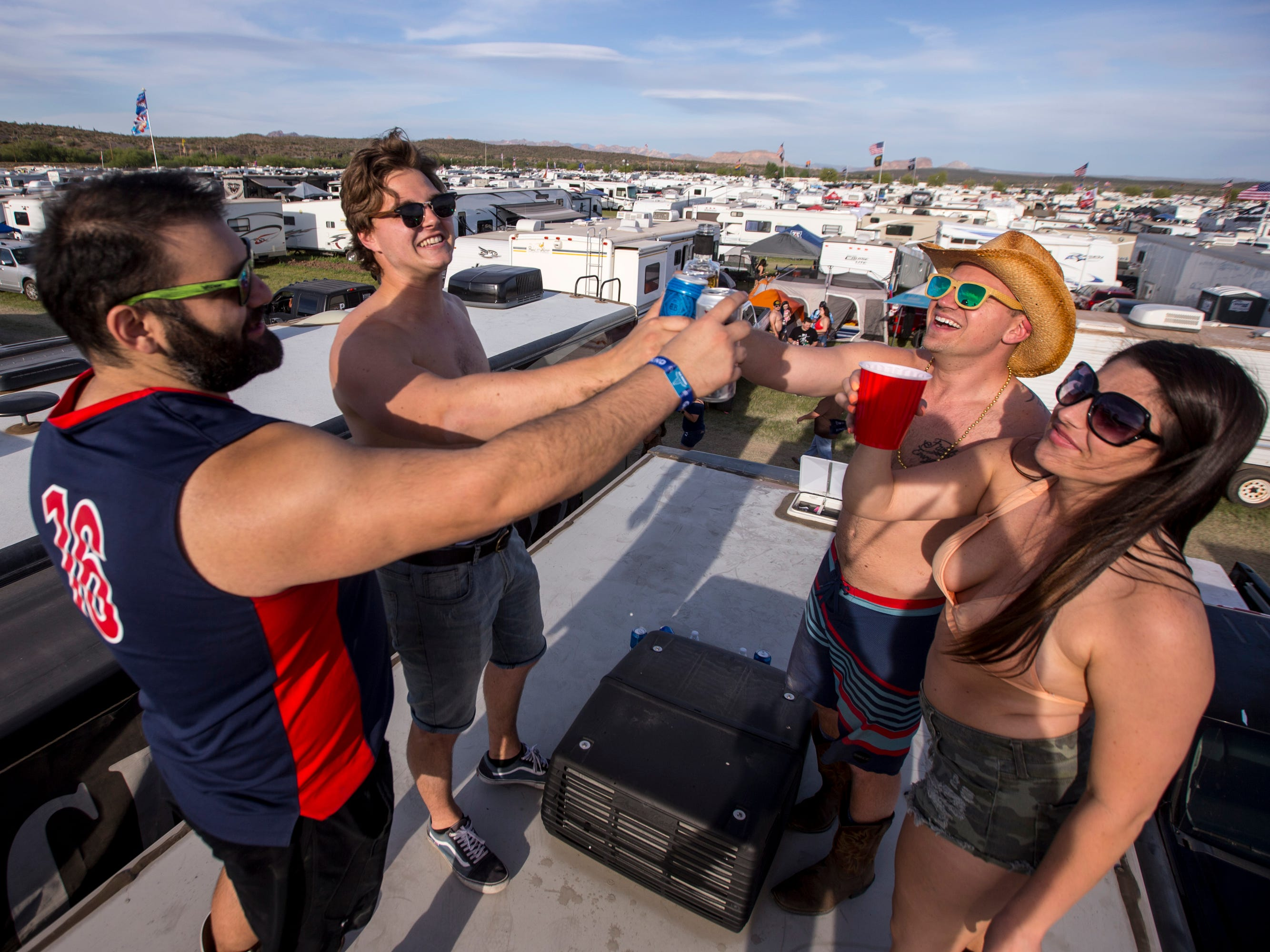 (from left to right) Miguel Perez, Anthony Johns, Max Zemezonak, and Jeanette Birk drink on top of their RV at the Crazy Coyote campsite  during Day 1 of Country Thunder Arizona on Apr. 11, 2019, in Florence, Ariz.