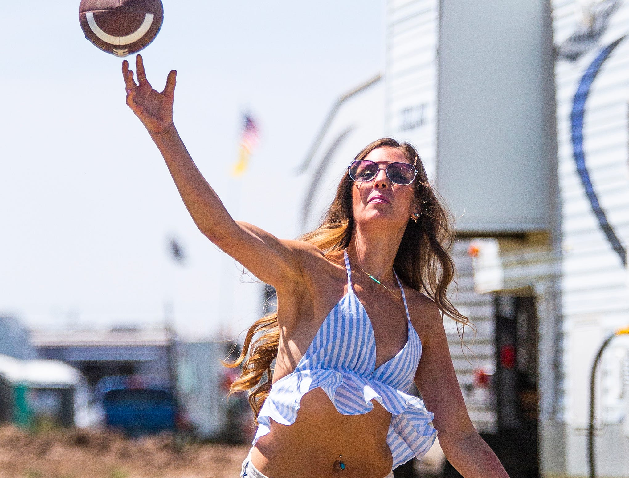 Paige Savage, 28, Mesa, tosses the football around in camp at the Country Thunder Arizona 2019 music festival, Thursday, April 11, 2019.