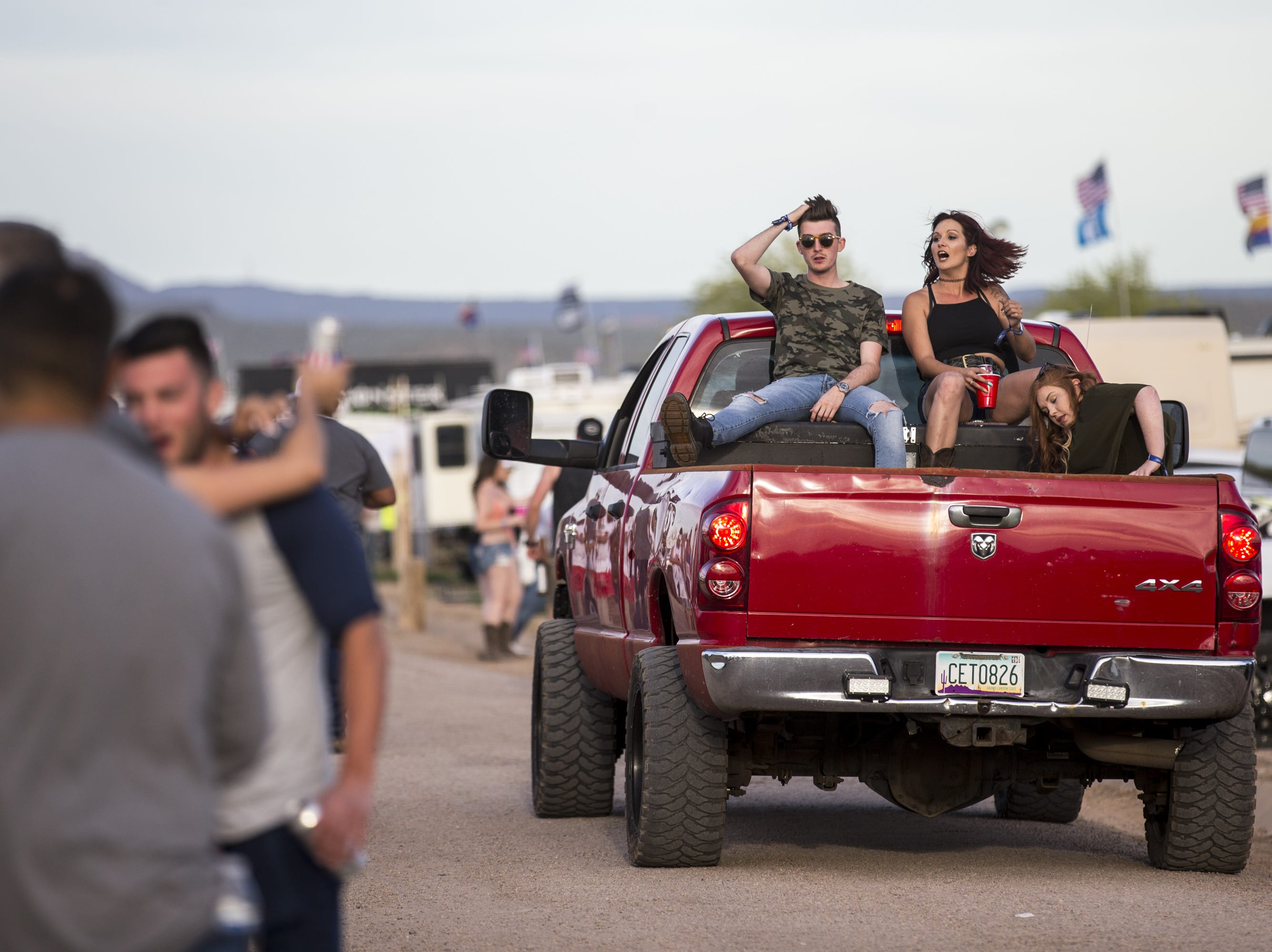 Festival-goers ride in the bed of a pickup truck outside the Crazy Coyote campsite on April 11, 2019, during Day 1 of Country Thunder Arizona in Florence.