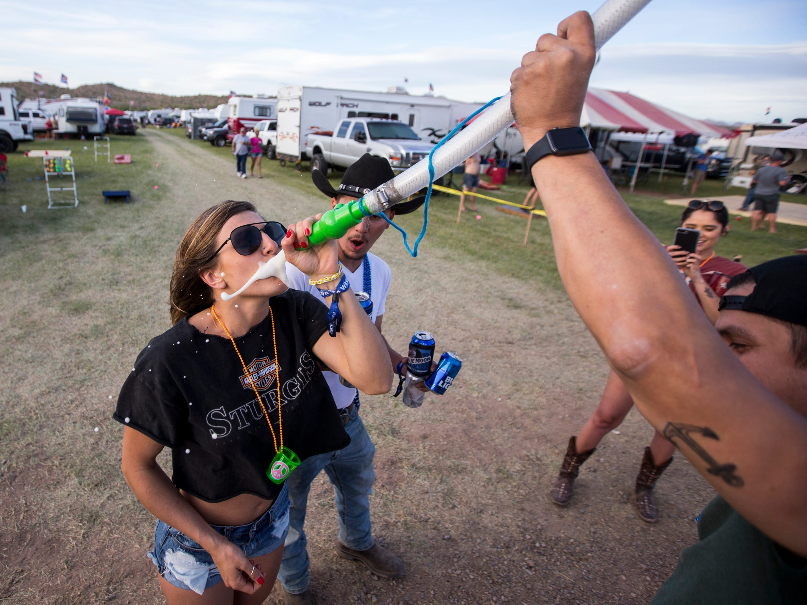 Felicia Farra drinks from a beer bong at the Crazy Coyote campsite during Day 1 of Country Thunder Arizona in Florence, Ariz., on Apr. 11, 2019.