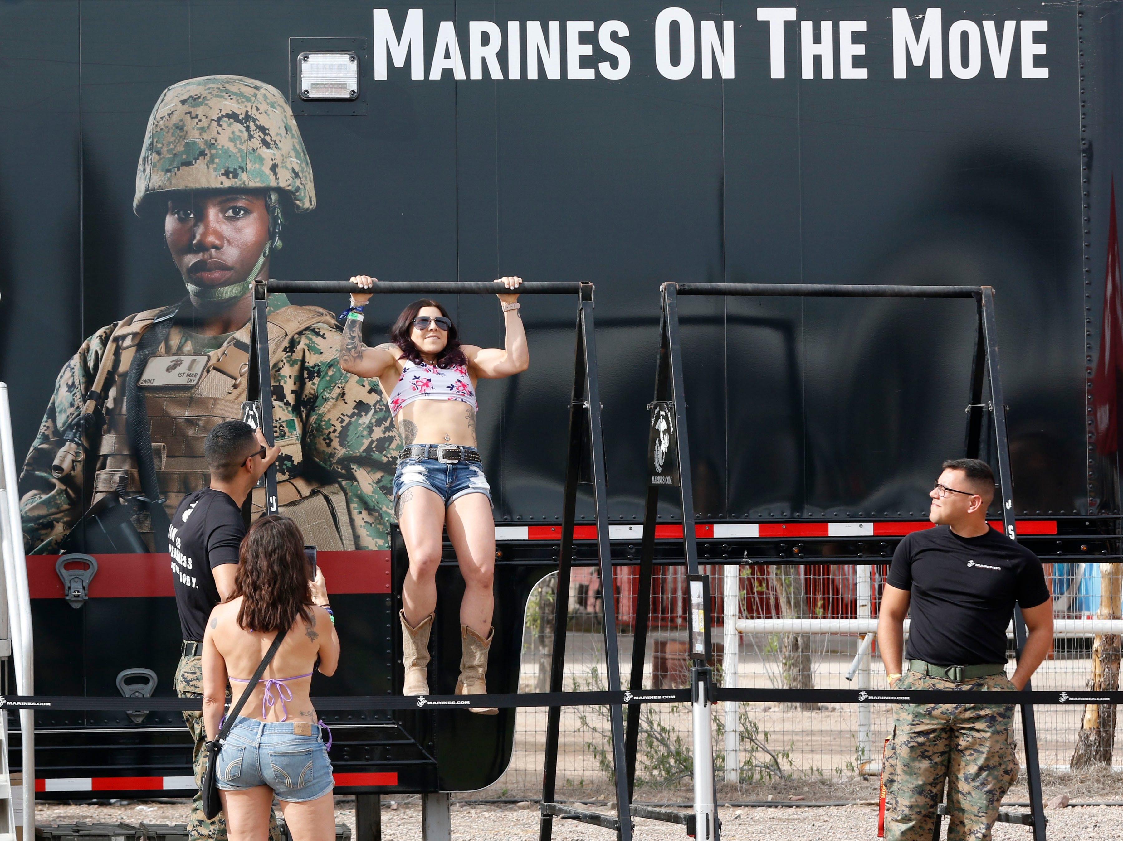 A Country & Western fan shows off her strength as she does a lot of pull-ups at the Marine's booth during Country Thunder Arizona on April 11, 2019, in Florence, Arizona.