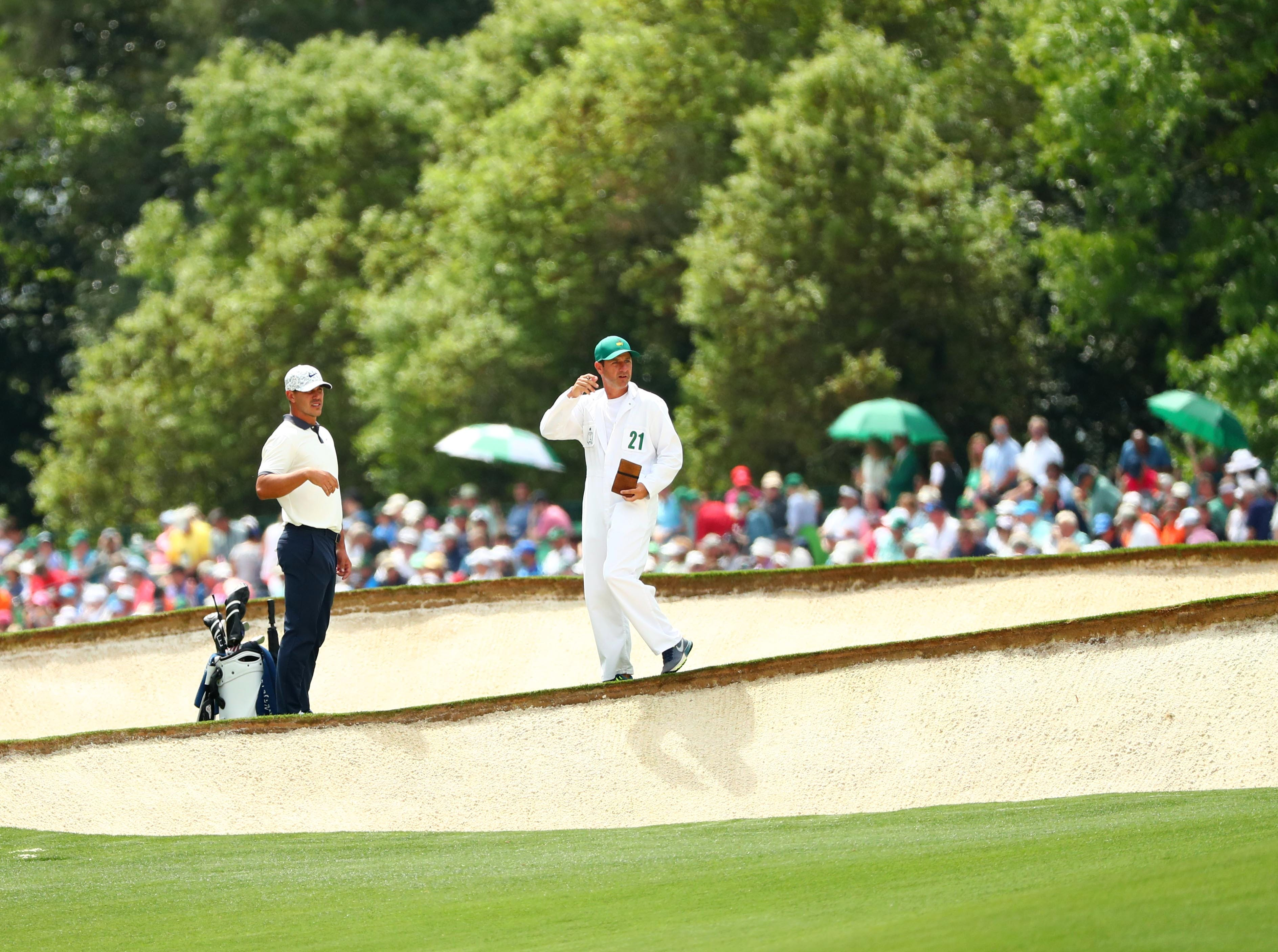 Apr 12, 2019; Augusta, GA, USA; Brooks Koepka and caddie Ricky Elliot in the bunkers on the 5th hole during the second round of The Masters golf tournament at Augusta National Golf Club. Mandatory Credit: Rob Schumacher-USA TODAY Sports