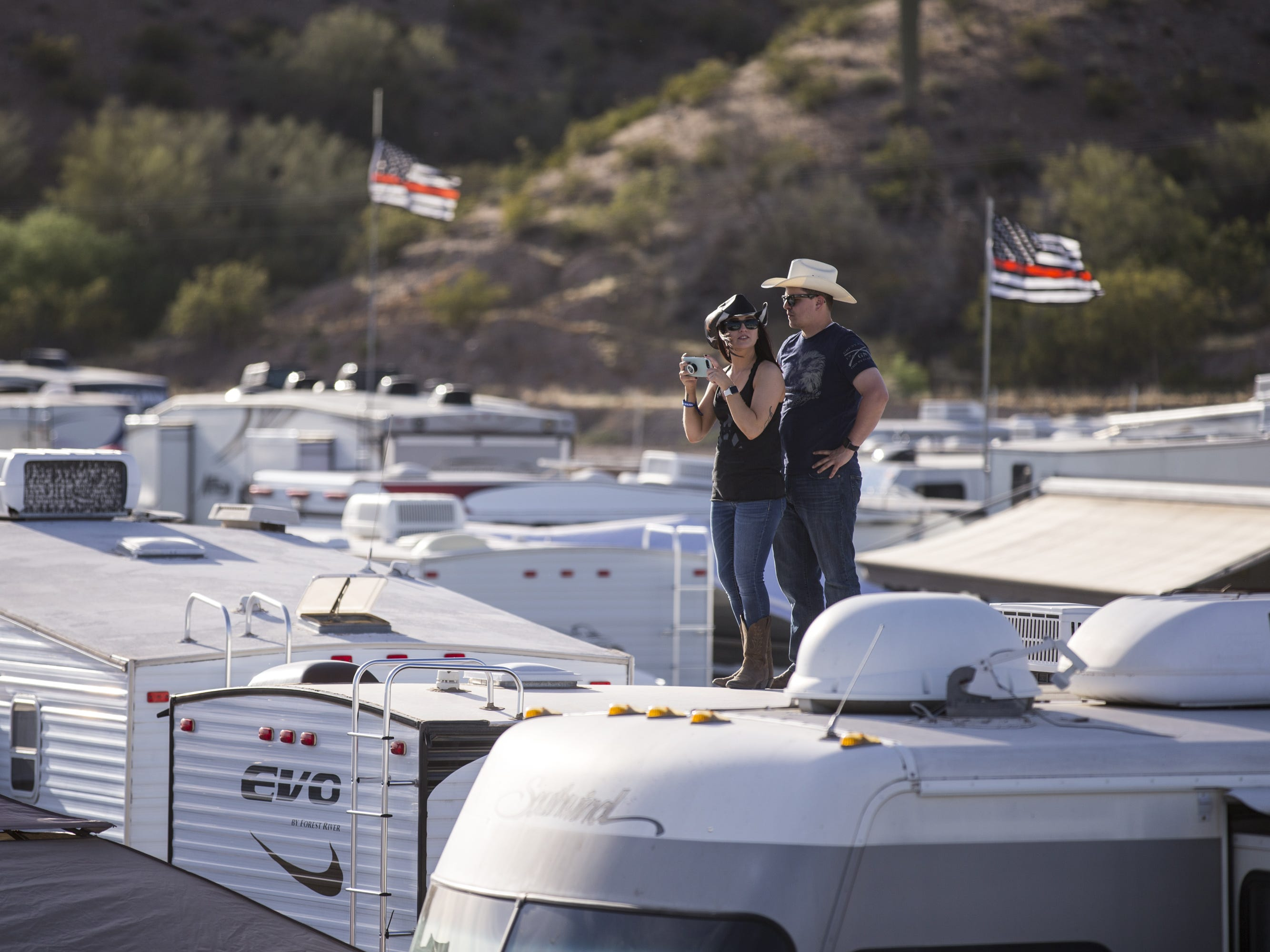 A couple stand on top of their RV at the Crazy Coyote campsite on April 11, 2019, during Day 1 of Country Thunder Arizona in Florence.