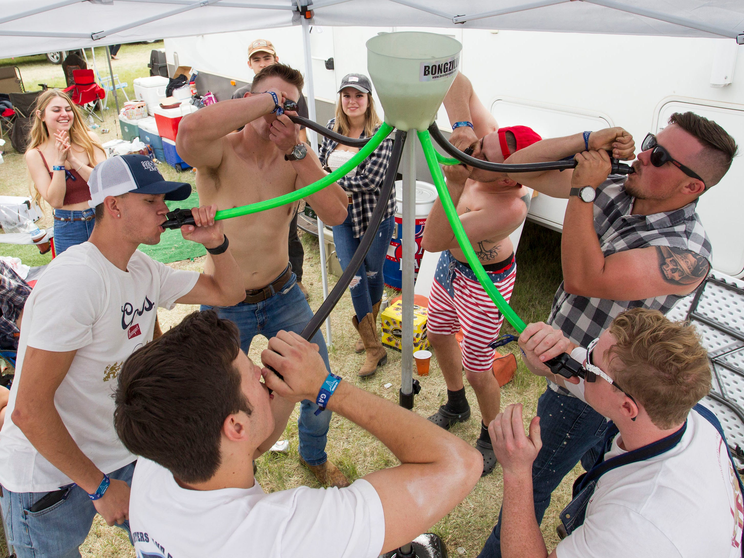 Boys from Tucson do a 10:30 a.m. Godzilla shot of beer during Country Thunder Arizona on April 12, 2019, in Florence, Ariz.