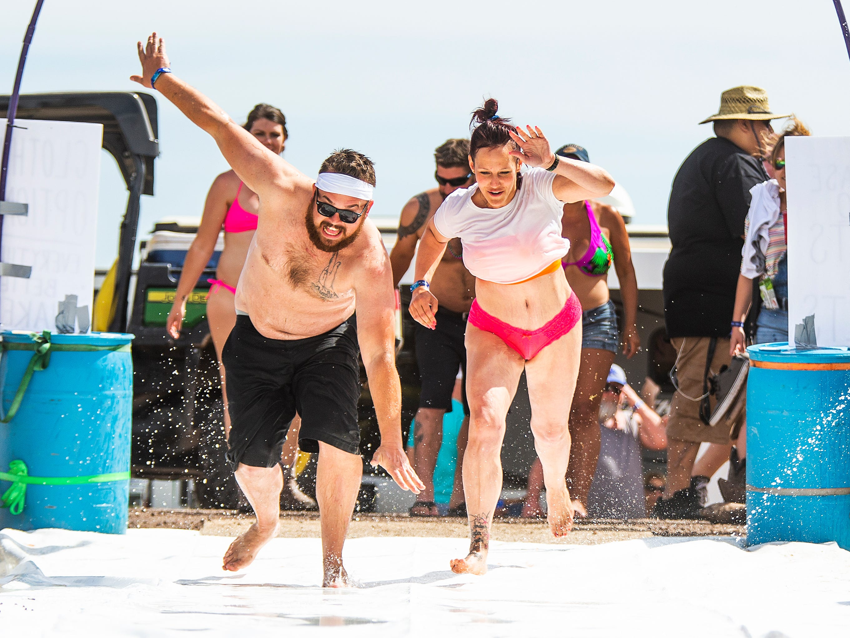 Zachary Brennan, 29, El Mirage, left, and Sara Dye, 30, Phoenix,try the slip and slide at Camp Crazy Coyote at the Country Thunder Arizona 2019 music festival outside Florence, Thursday, April 11, 2019.