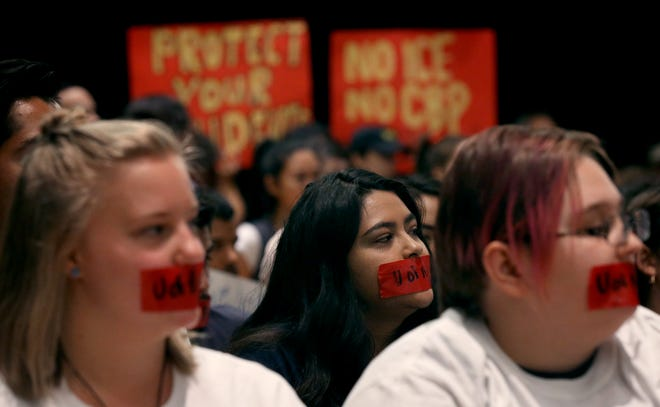 Some of the 300 crowding into the Arizona Board of Regents meeting at the U of A wear tape over their mouths to protest the citing of three students last month of interfering with the peaceful of an educational institution on April 11, 2019, in Tucson, Ariz.