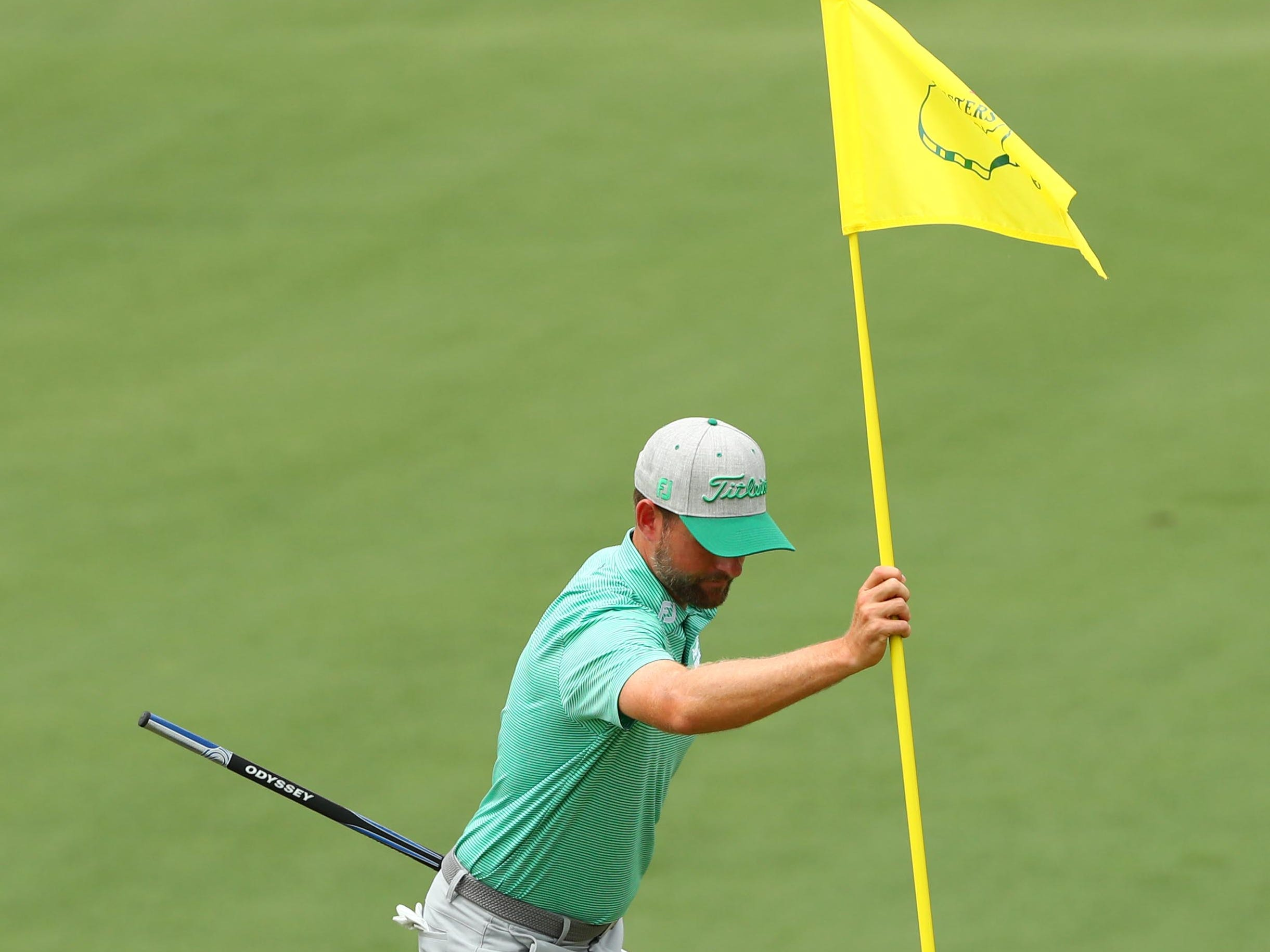 Apr 12, 2019; Augusta, GA, USA; Webb Simpson removes the flag from the 2nd hole during the second round of The Masters golf tournament at Augusta National Golf Club. Mandatory Credit: Rob Schumacher-USA TODAY Sports