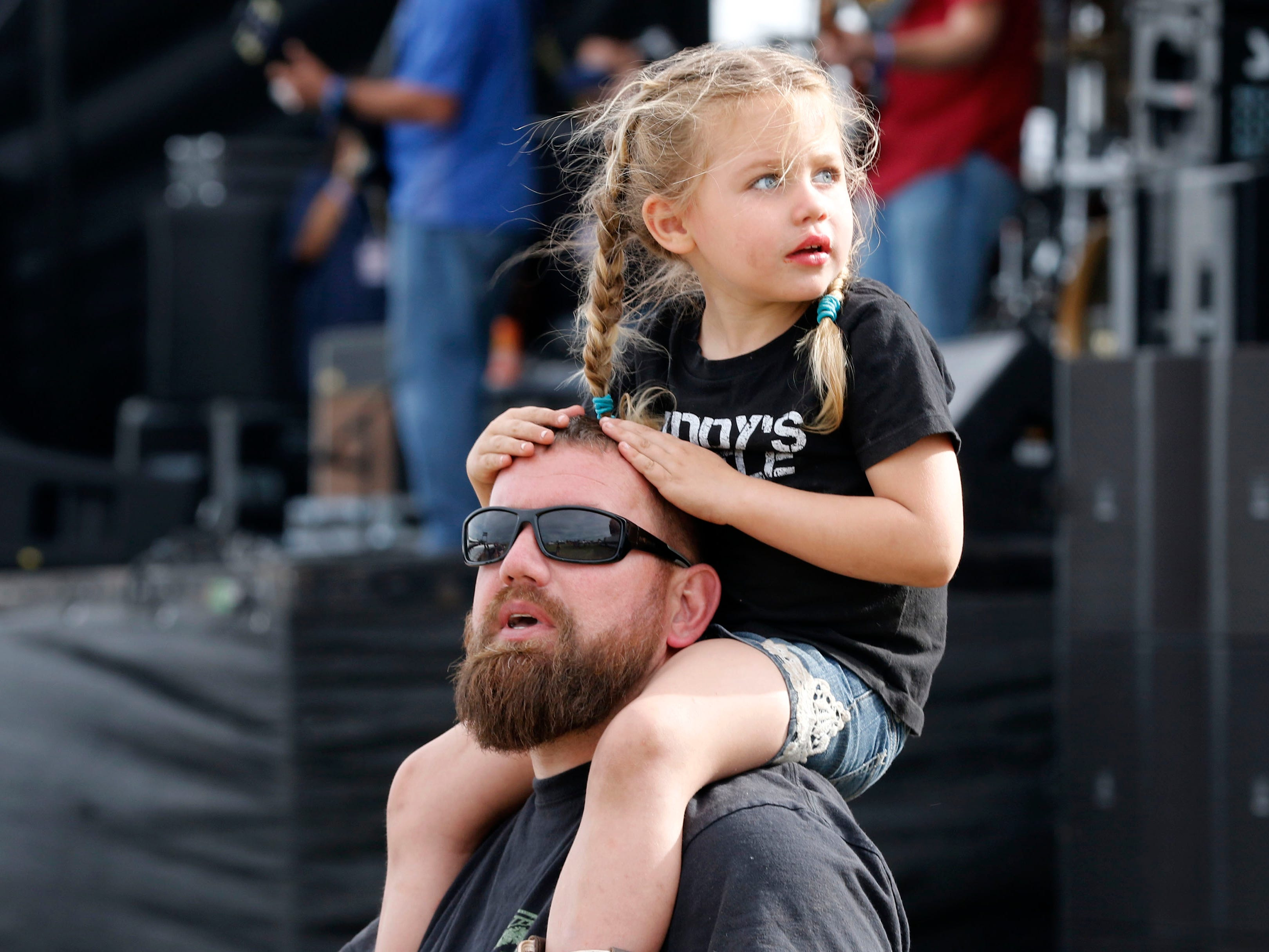 There's so much to look at during Country Thunder Arizona. Tom Frohn looks one way as daughter Kaycee 4, looks the other as The Cole Trains play on April 11, 2019, in Florence, Arizona.