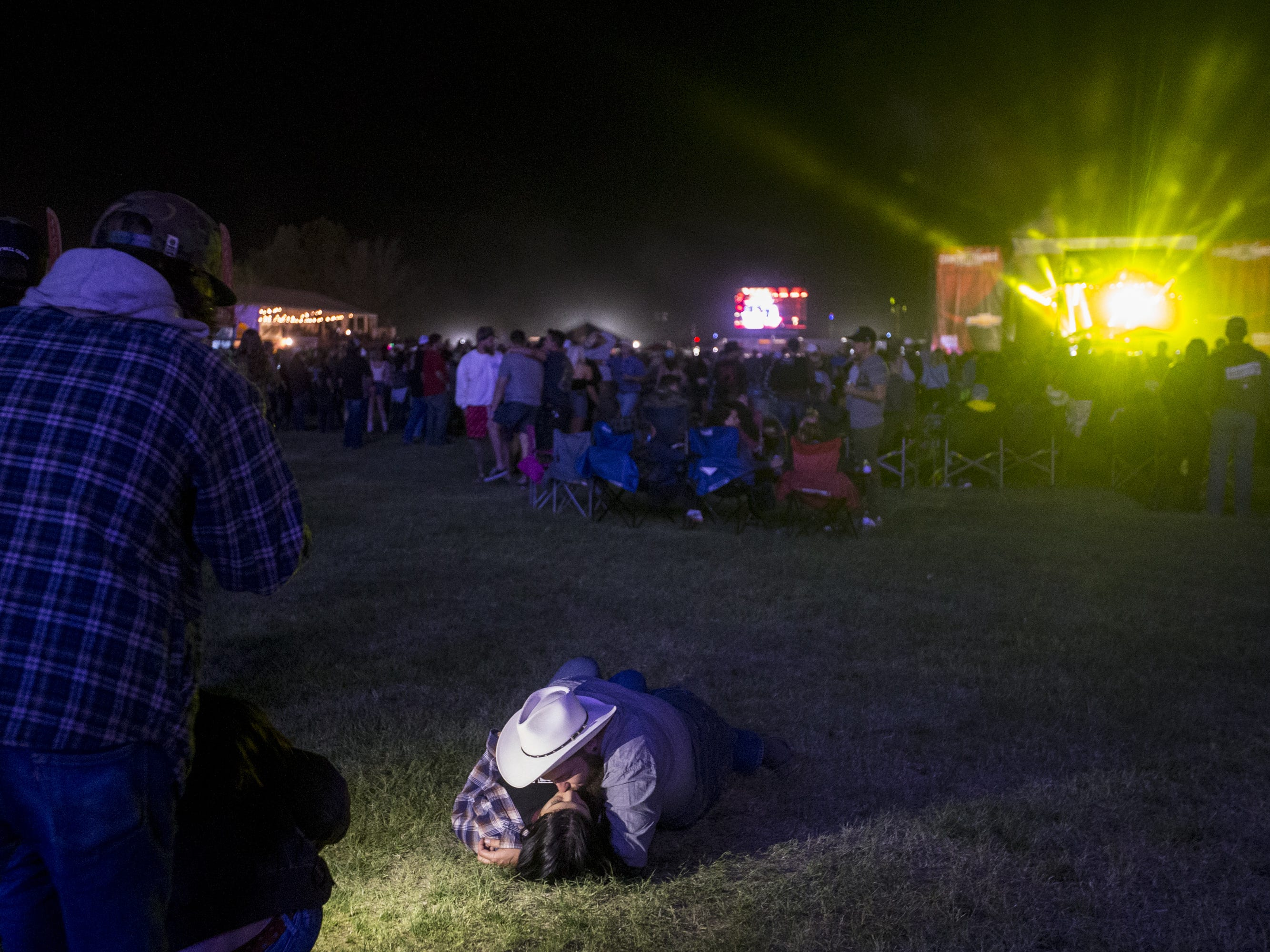 Tyler Lippert kisses Madison Maestas while Trace Adkins performs on April 11, 2019, during Day 1 of Country Thunder Arizona in Florence.