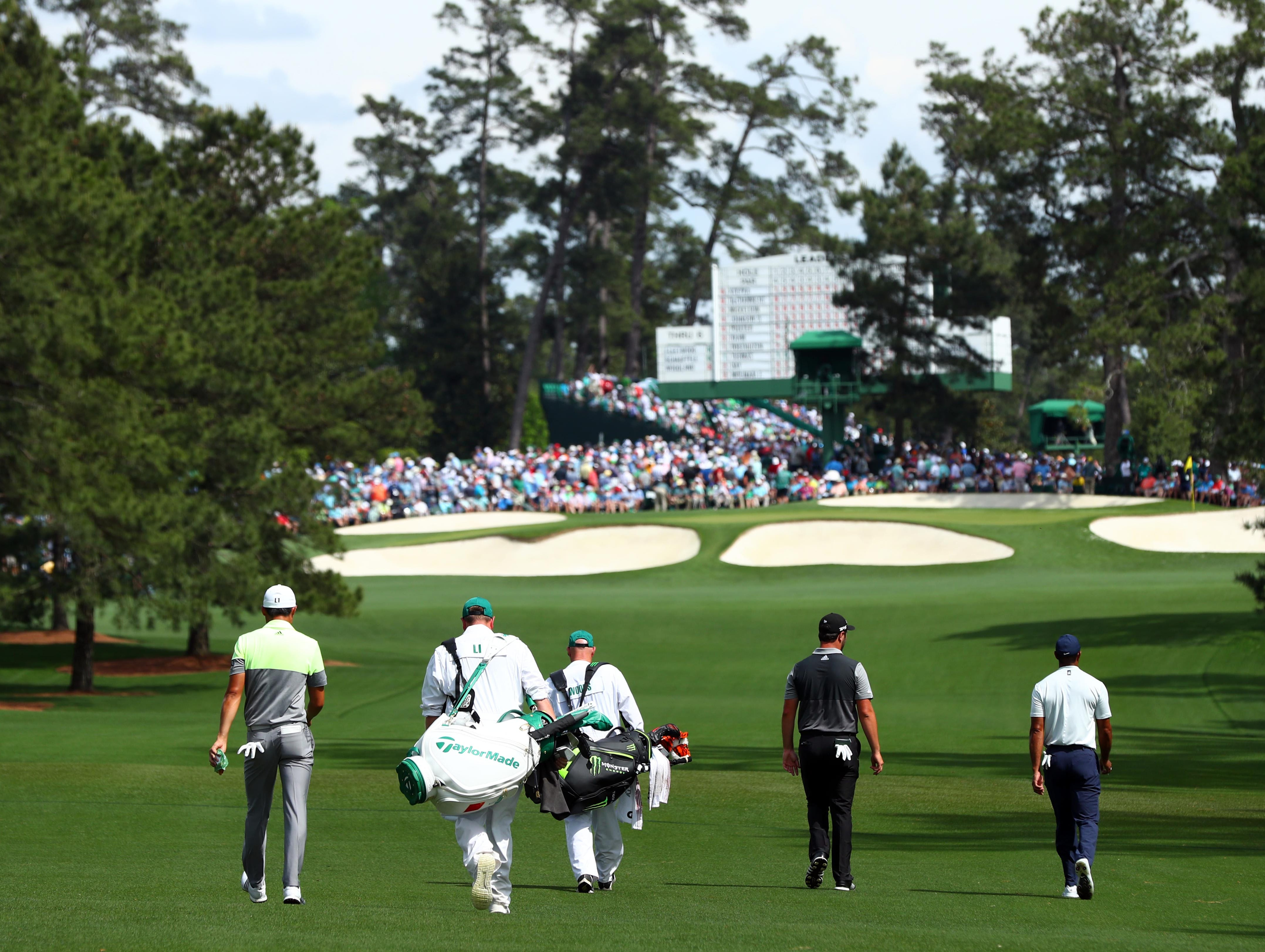 Apr 12, 2019; Augusta, GA, USA; Haotong Li , Jon Rahm and Tiger Woods walk the 7th fairway during the second round of The Masters golf tournament at Augusta National Golf Club. Mandatory Credit: Rob Schumacher-USA TODAY Sports
