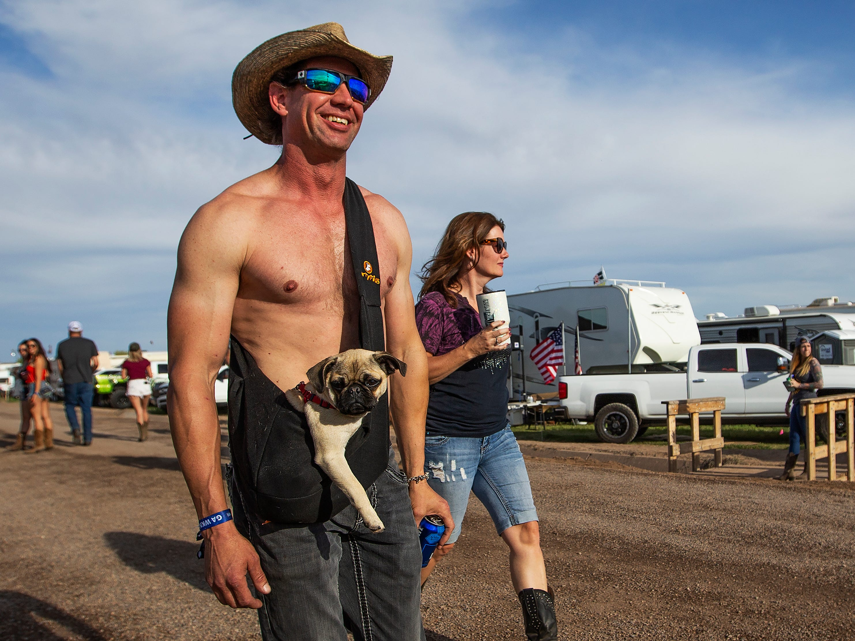 "Dan Lundell, 35, Mesa, carries his pug puppy ""Zoey"" as he strolls around the  Crazy Coyote campground at the Country Thunder Arizona 2019 music festival, on April 11, 2019."