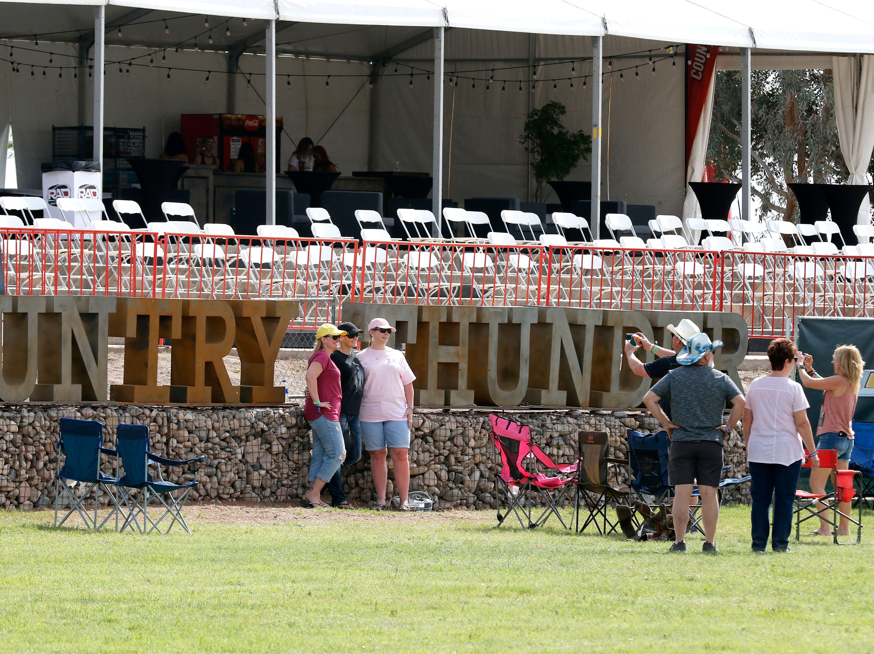 Country and Western music lovers pose in front of the Country Thunder sign during Country Thunder Arizona on April 11, 2019, in Florence, Arizona.
