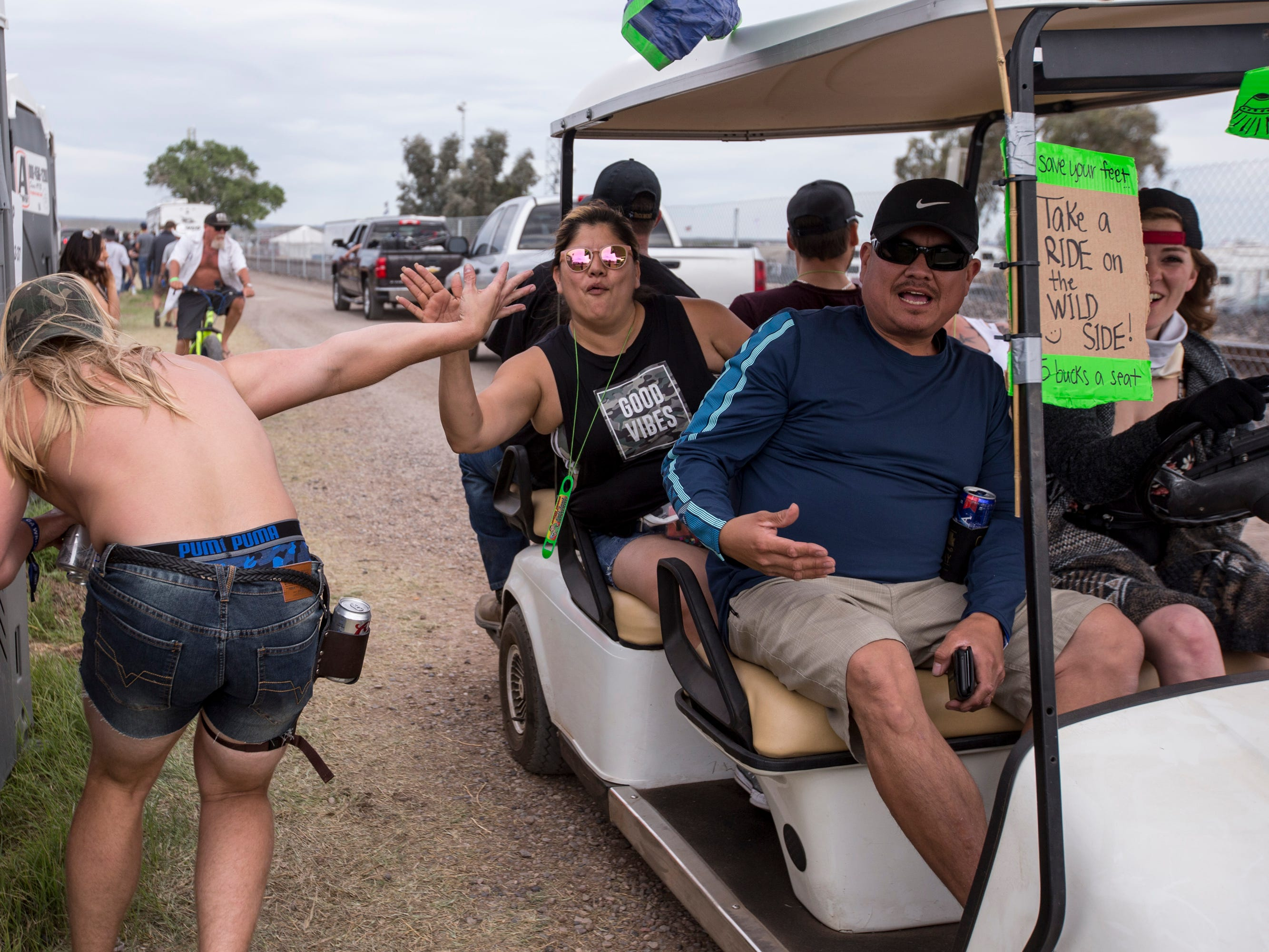 Dane Dale high fives people on a golf cart during Day 1 of Country Thunder Arizona in Florence, Ariz., on Apr. 11, 2019.