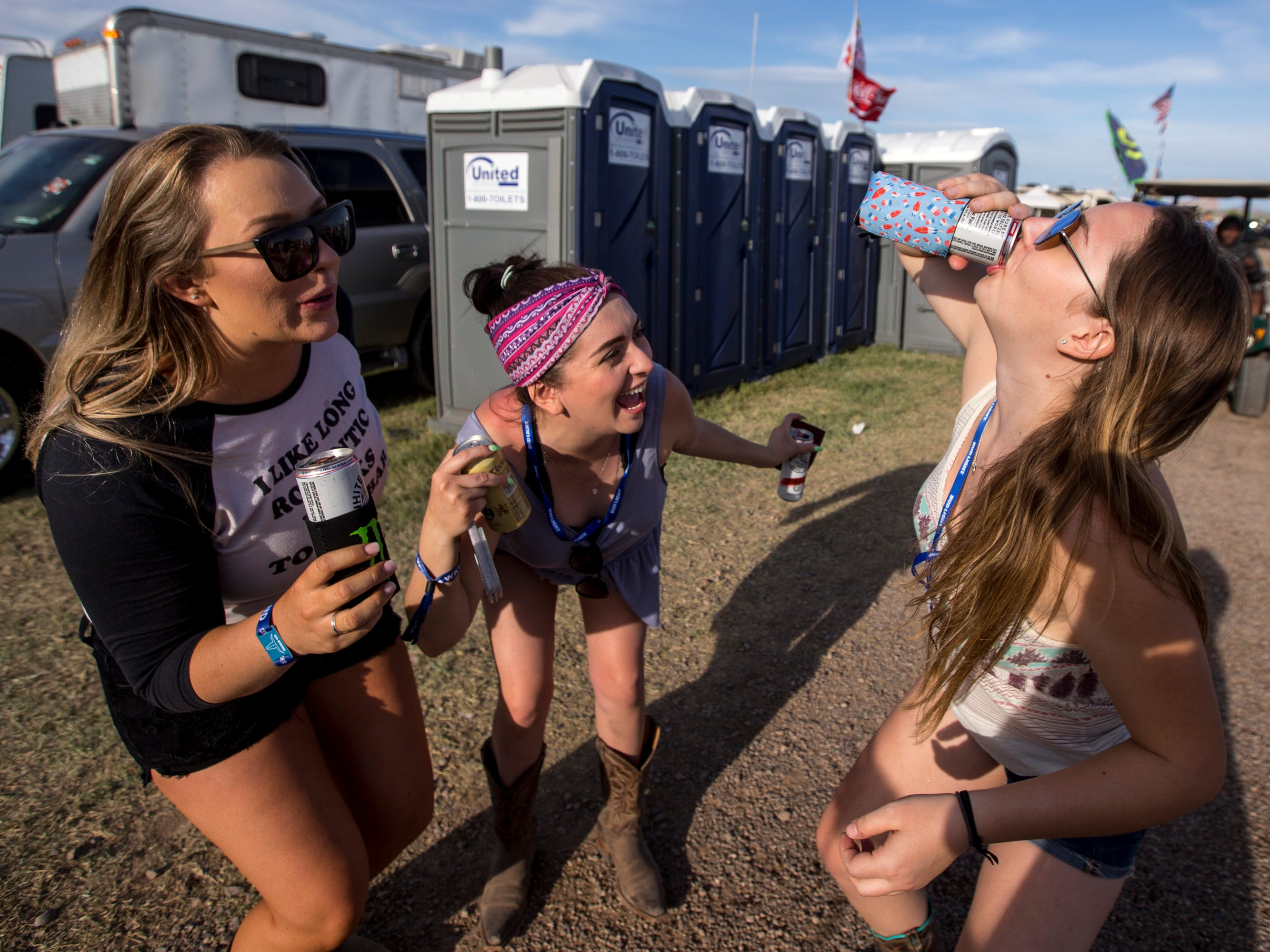 (from left to right) Dakota Starlin and Miriam Yepiz watch Mary Jacobs drink a spiked seltzer at the Crazy Coyote campsite during Day 1 of Country Thunder Arizona in Florence, Ariz., on Apr. 11, 2019.