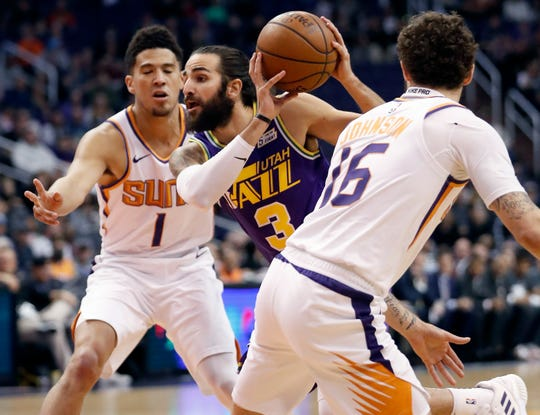 Utah Jazz guard Ricky Rubio (3) drives as Phoenix Suns guard Devin Booker (1) and guard Tyler Johnson (16) defend during the first half of an NBA basketball game, Wednesday, March 13, 2019, in Phoenix. (AP Photo/Matt York)