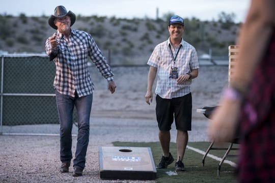 Trace Adkins plays corn hole with Chad Mitchell of KMLE on April 11, 2019, during Day 1 of Country Thunder Arizona in Florence.