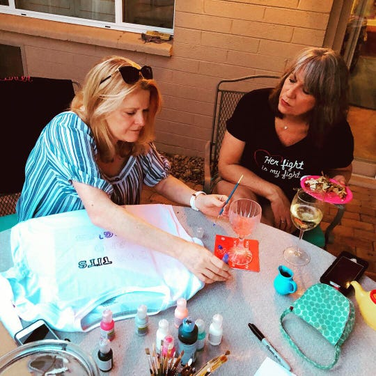 Keira, the consoler, and Karina, the optimist, work on T-shirts in support of Catherine.