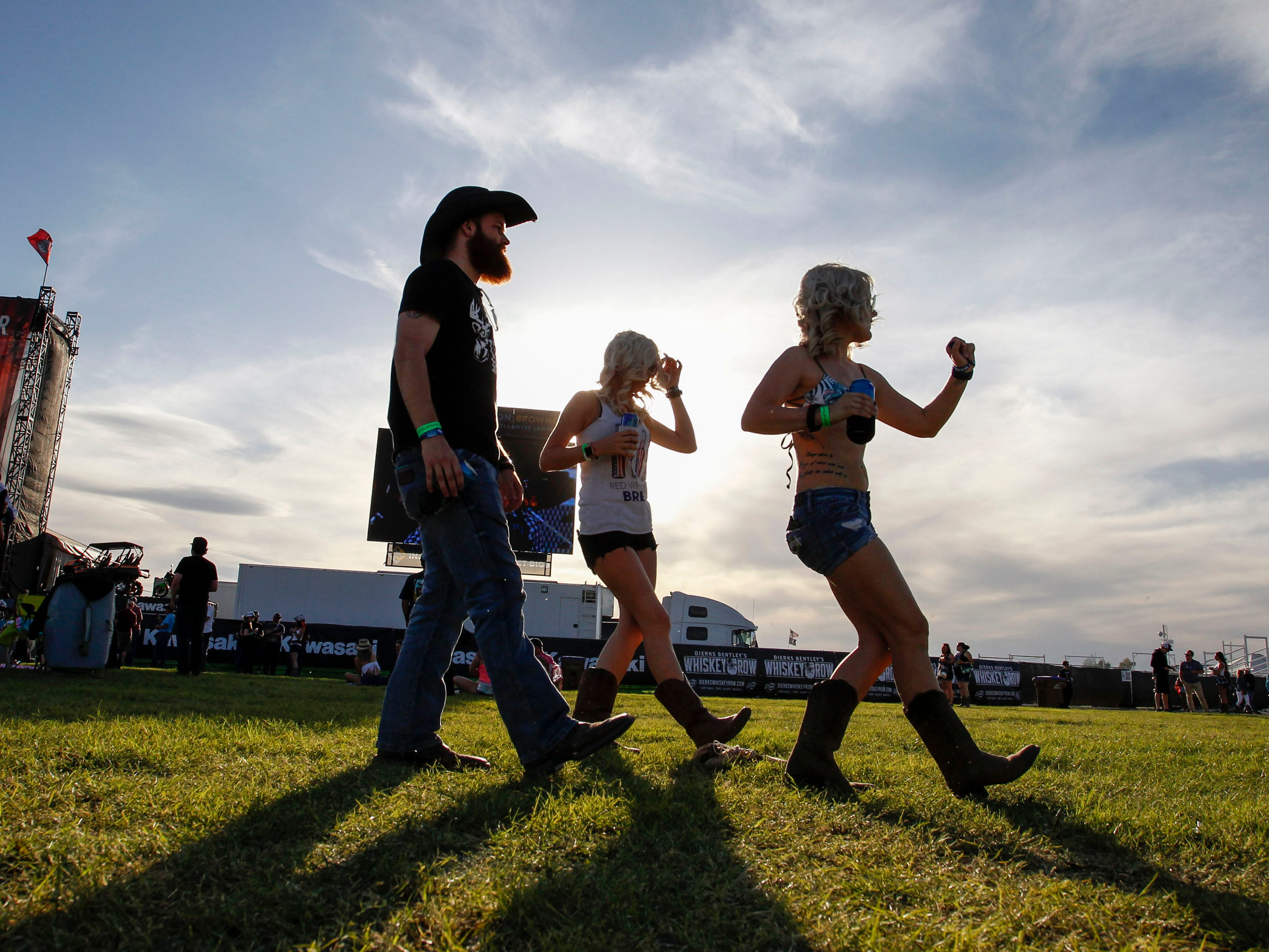 Brad Eckburg, Tiffani Brooks and Brittany Bowman dance as the sun prepares to set during Country Thunder Arizona on April 11, 2019, in Florence, Arizona.