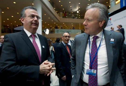 El dirigente del Banco Central de México, Alejandro Díaz de León, conversa con su contraparte canadiense Stephen Poloz.