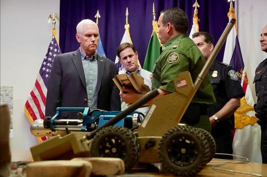 Mike Pence (izq.) junto al gobernador de Arizona Doug Ducey (centro), dialogan con un agente fronterizo durante su visita por Nogales.