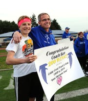 Cedar Crest track and field coach Rob Bare and his son Zach celebrate Bare's 200th victory as the Falcons' boys coach after Thursday's win over Lebanon.