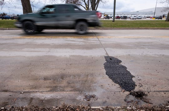 A truck drives past a recently patched pothole on Huron Avenue Friday, April 12, 2019 in Marysville. This year, the county has only used 214.8 tons of cold patch, which is down from last year's 637.65 tons, according to St. Clair County Road Commission Managing Director Kirk Weston.