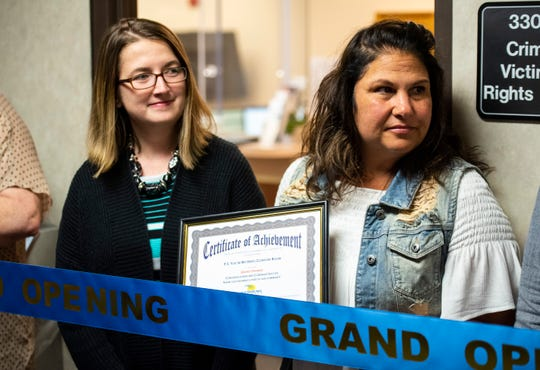 Mara McCalmon, right, a violent crime survivor and founder of P.S. You're My Hero, holds a certificate of achievement given to her during a ribbon cutting ceremony for the P.S. You're My Hero Comfort Room, held Friday, April 12, 2019 at the St. Clair County Courthouse.