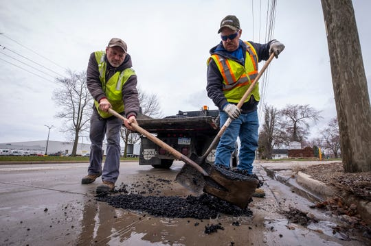 Marysville DPW utility workers Mike Tosch, left, and Randy Smith work to patch a pothole along Huron Avenue in Marysville Friday, April 12, 2019.  Officials are saying this year's pothole season isn't as bad as prior years due to this spring's slower thaw.