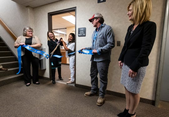 Mara McCalmon, center, a violent crime survivor and founder of P.S. You're My Hero, cuts the ribbon for the P.S. You're My Hero Comfort Room with victims rights advocate Cortney Carl, second from left, during a ceremony held Friday, April 12, 2019 at the St. Clair County Courthouse.