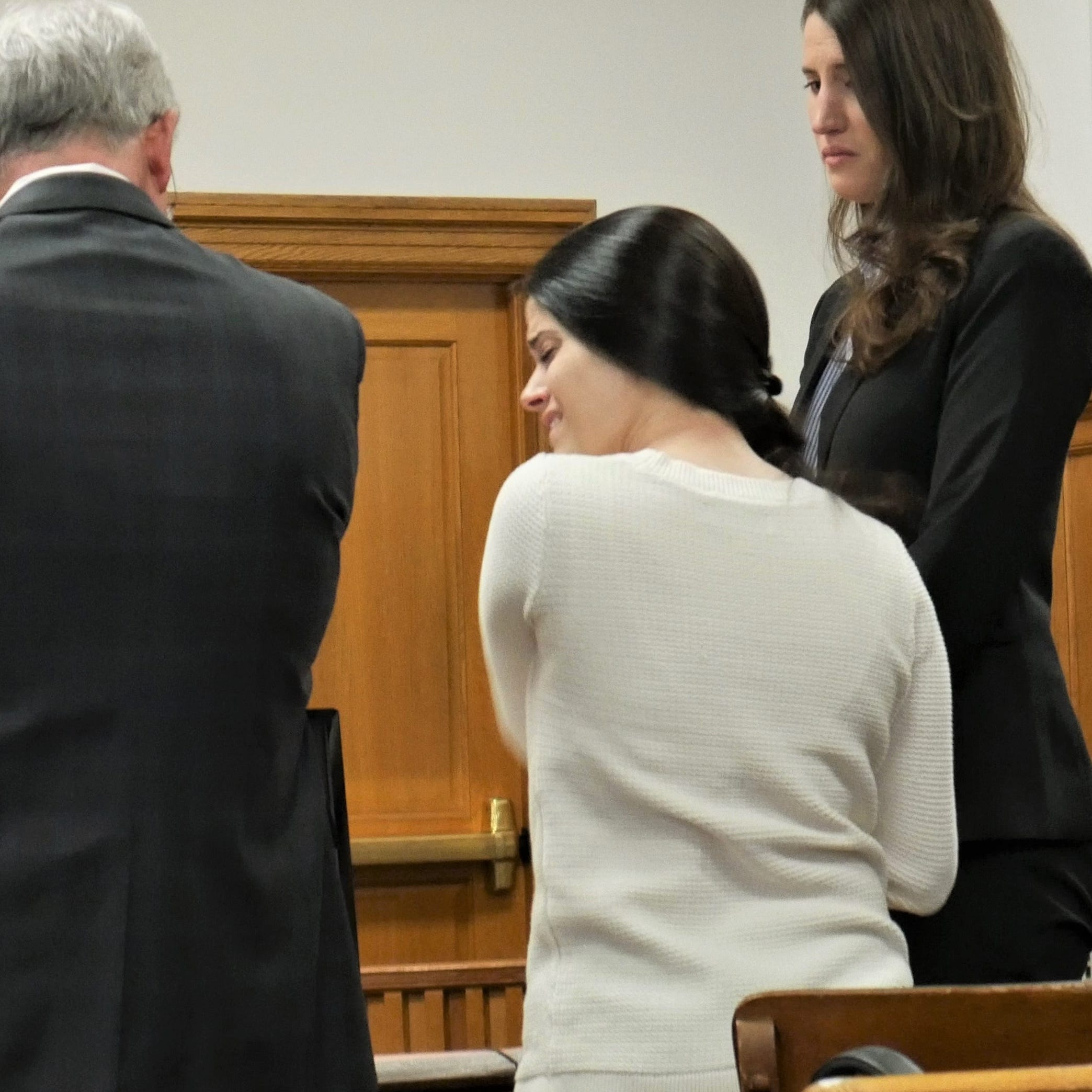 Nicole Addimando (center) stands with members of her defense team and cries as she removes a necklace, after a Dutchess County jury returned a guilty verdict for second-degree murder on April 12, 2019.