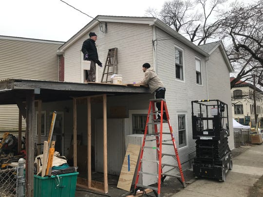 Scenic artists Joel Ossenfort of Brooklyn, left, and Michael Hurt of New Paltz, preparing a house on Delafield Street in the City of Poughkeepsie for the filming of an HBO series starring Mark Ruffalo.