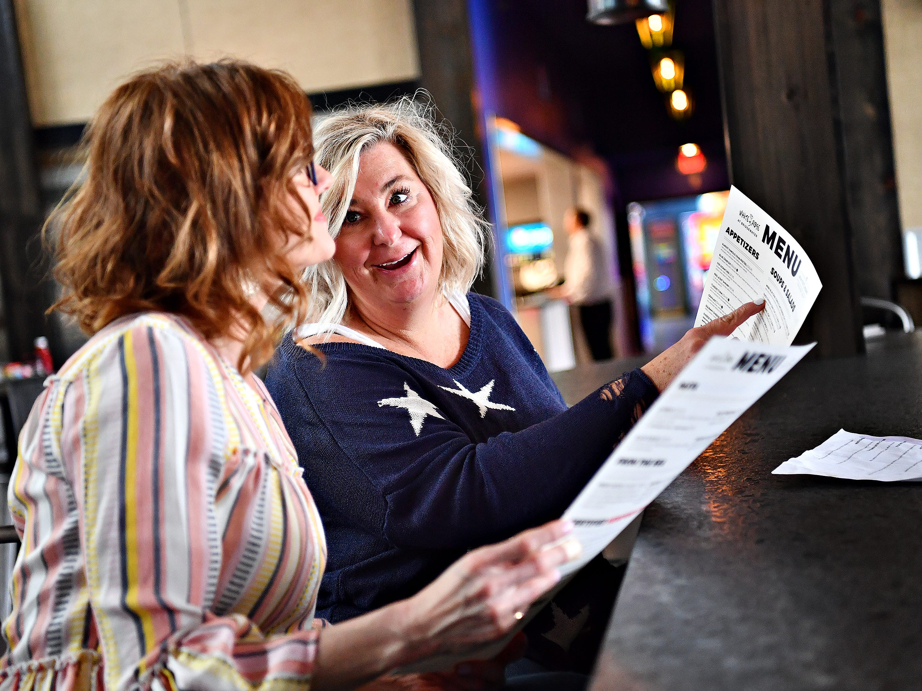 Amy Curran, back, and Liz Orendorf, both of York Township, discuss the menu while dining for lunch at White Rose at Bridgewater, which overlooks the Bridgewater Golf Course in York Township, Friday, April 12, 2019. Curran, who lives nearby, says she was at the restaurant the previous night and planned to dine there again for dinner on Friday. Dawn J. Sagert photo