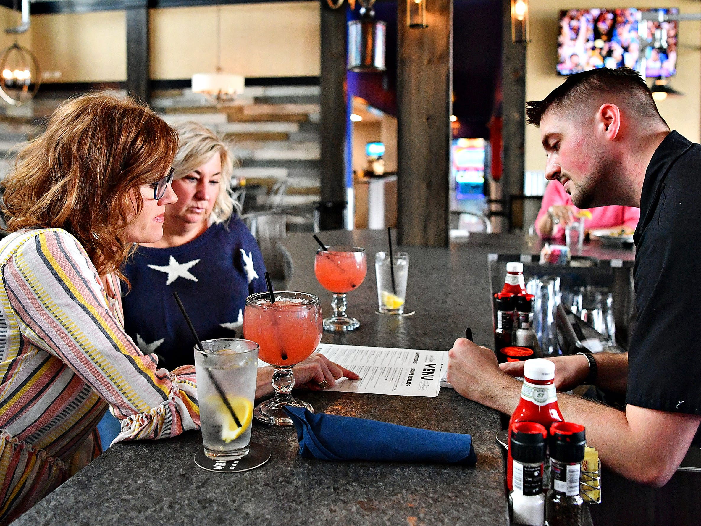 From left, Liz Orendorf and Amy Curran, both of York Township, place their order with Bartender Bradley Clarkson while dining for lunch at White Rose at Bridgewater, which overlooks the Bridgewater Golf Course in York Township, Friday, April 12, 2019. Dawn J. Sagert photo