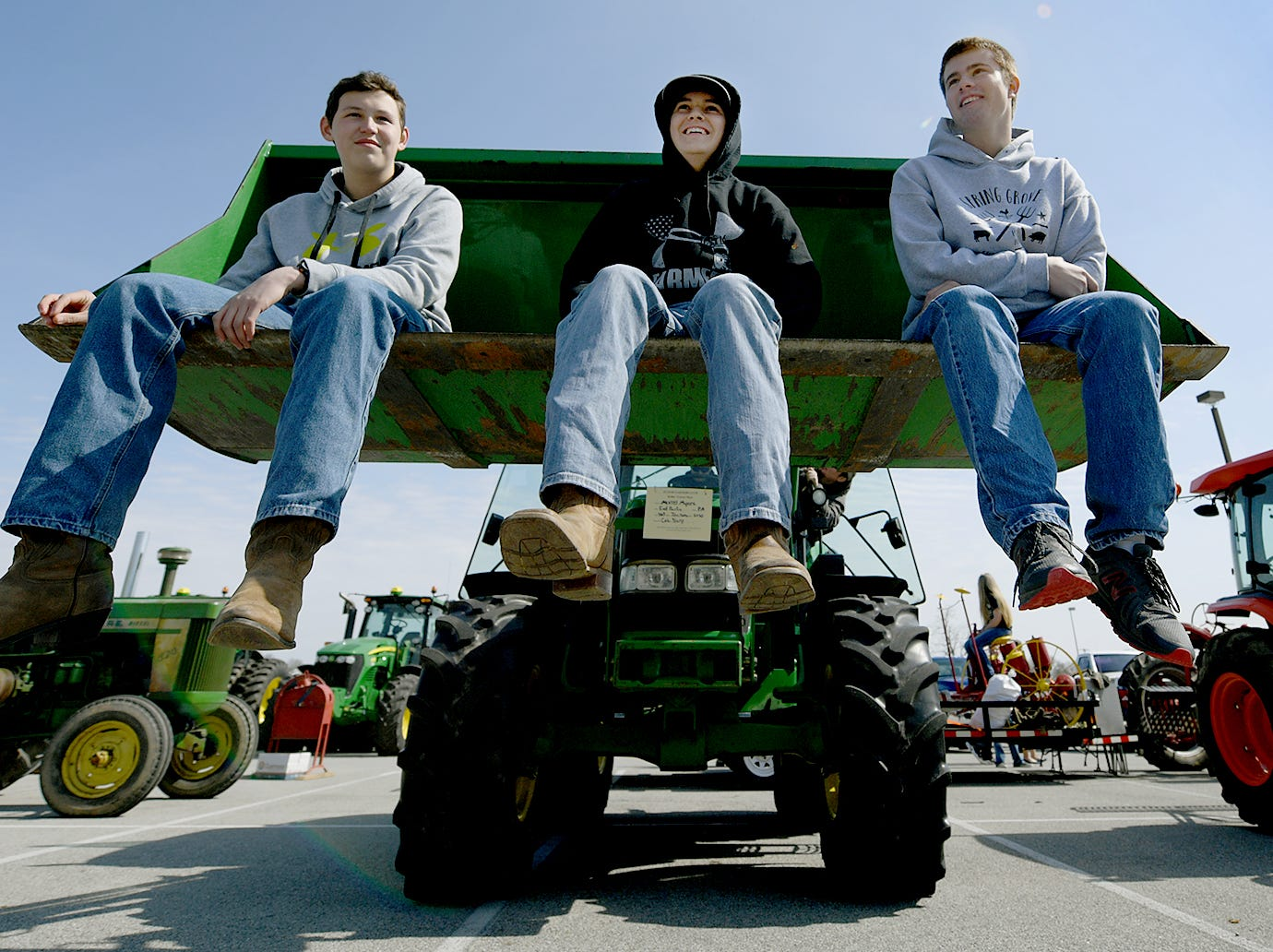 Future Farmers Club members, from left, freshman Wyatt Baker, sophomore Chase Young and freshman Brandon Mummert sits in a tractor bucket while helping out during the district's 6th Annual Rollin' Tractor Show Thursday, April 11, 2019. The show is presented by the Future Farmers Club. Alumni and area residents brought farm equipment to display with the goal of acquainting students with the agriculture industry. The show, which included a parade of equipment, visited the intermediate and elementary schools. Bill Kalina photo