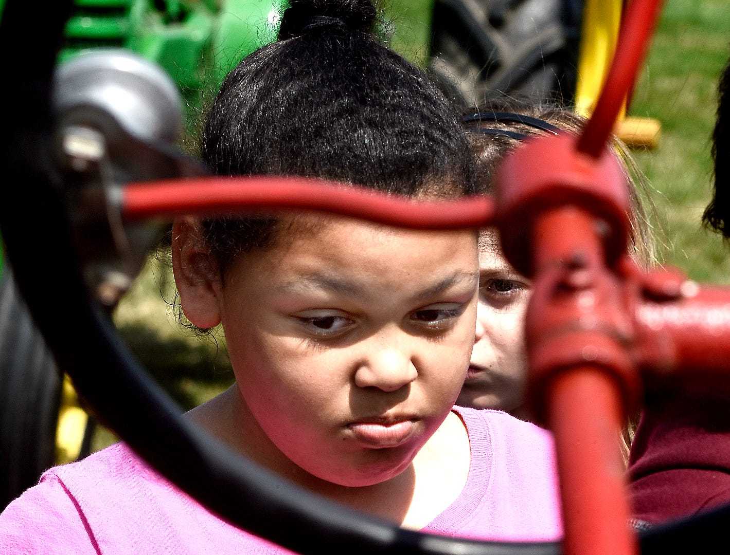 Spring Grove Elementary fourth grader Kyra Williams participates in a demonstration during the district's 6th Annual Rollin' Tractor Show Thursday, April 11, 2019, presented by the Future Farmers Club. Alumni and area residents brought farm equipment to display with the goal of acquainting students with the agriculture industry. The show, which included a parade of equipment, visited the intermediate and elementary schools. Bill Kalina photo