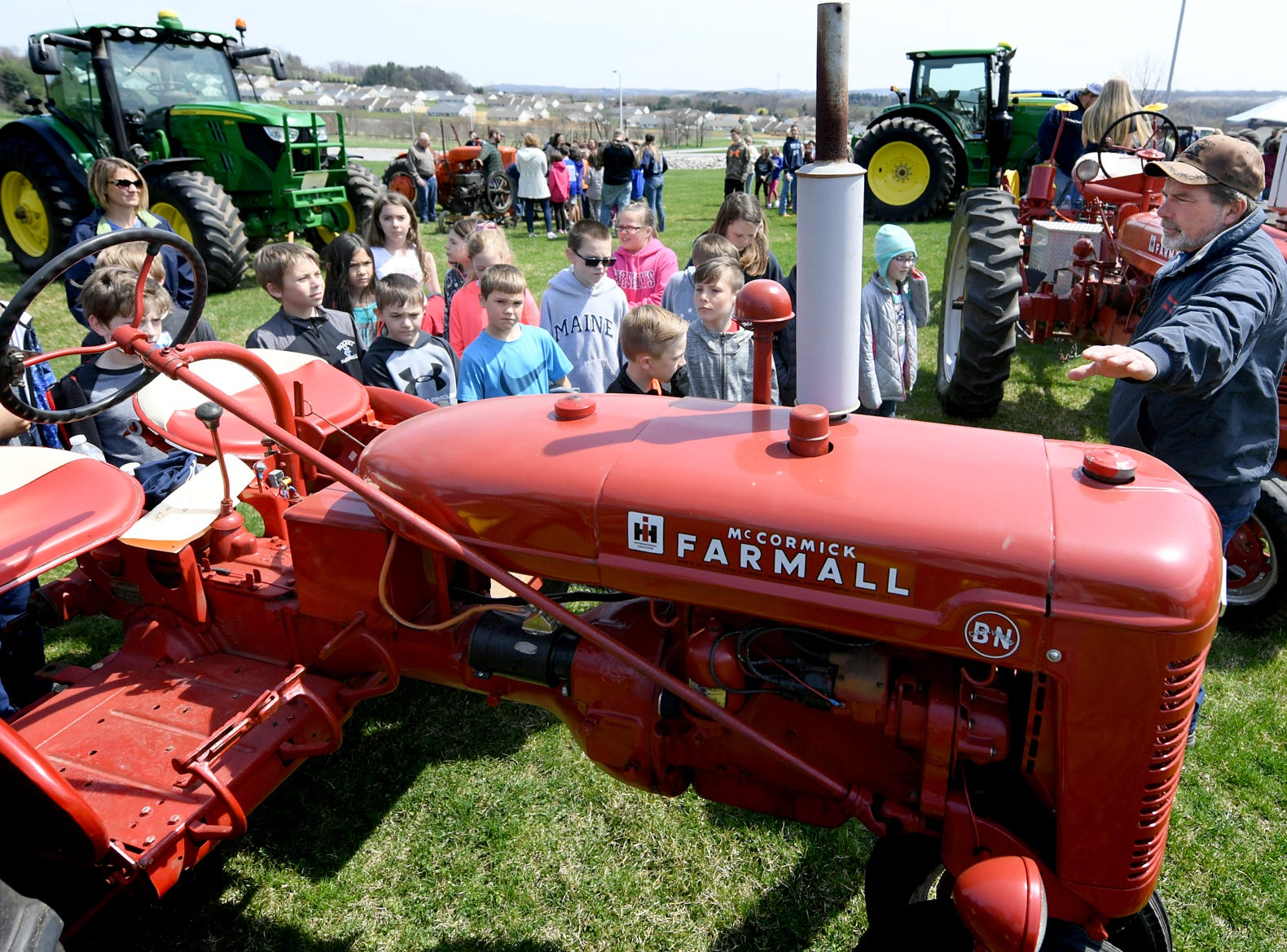 Carey Waugh of Shrewsbury Township talks to Spring Grove Elementary School fourth graders about the 1947 Farmall tractor he was showing during the district's 6th Annual Rollin' Tractor Show Thursday, April 11, 2019. The show is presented by the Future Farmers Club. Alumni and area residents brought farm equipment to display with the goal of acquainting students with the agriculture industry. The show, which included a parade of equipment, visited the intermediate and elementary schools. Bill Kalina photo