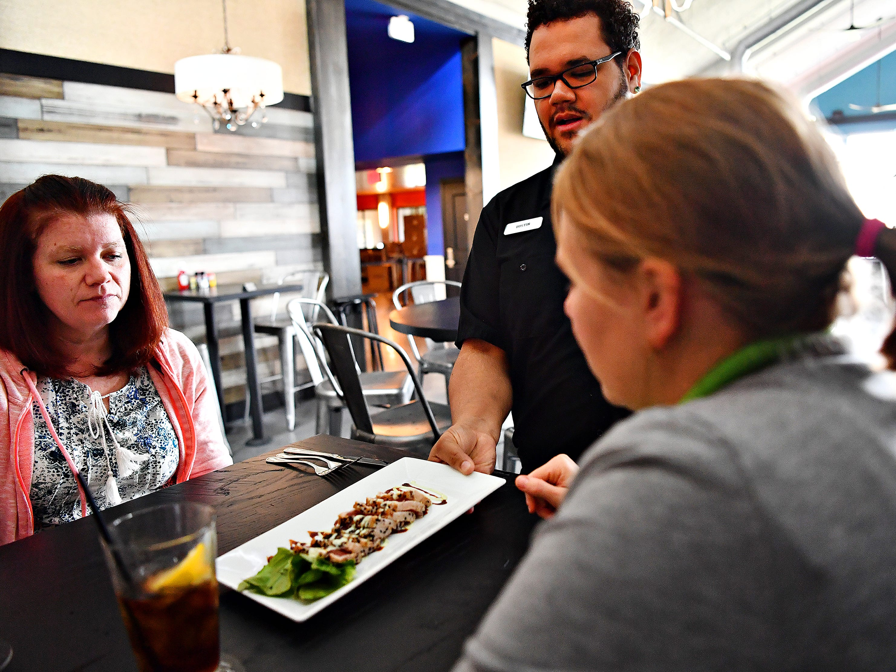 Katie Schultz, left, of Hampstead, Md., and Jaime Smetana, of Springettsbury Township, are served their appetizer of Gravlax (smoked salmon) by Server Dustin Rhoades, while dining for lunch at White Rose at Bridgewater, which overlooks the Bridgewater Golf Course in York Township, Friday, April 12, 2019. Dawn J. Sagert photo