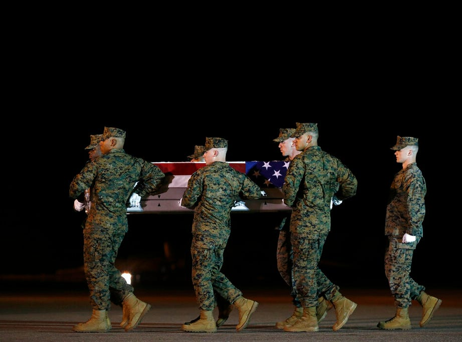 A U.S. Marine Corps carry team moves a transfer case containing the remains of Staff Sgt. Christopher A. Slutman, Thursday, April 11, 2019, at Dover Air Force Base, Del. According to the Department of Defense, Slutman, of Newark, Del., was among three American service members killed by a roadside bomb on Monday, April 8, 2019, near Bagram Airfield in Afghanistan. (AP Photo/Patrick Semansky)