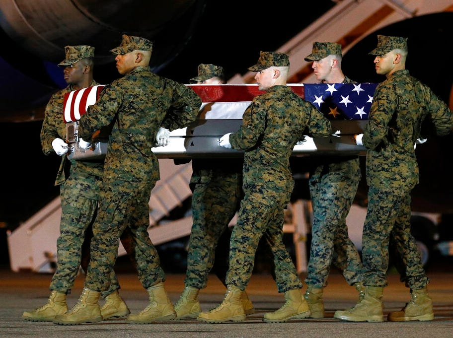 A U.S. Marine Corps carry team moves a transfer case containing the remains of Staff Sgt. Christopher Slutman, Thursday, April 11, 2019, at Dover Air Force Base, Del. According to the Department of Defense, Slutman, of Newark, Del., was among three American service members killed by a roadside bomb on Monday, April 8, near Bagram Airfield in Afghanistan. (AP Photo/Patrick Semansky)