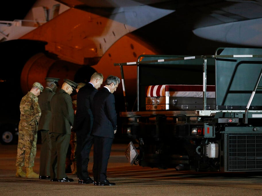 Delaware Gov. John Carney, right, acting Defense Secretary Patrick Shanahan, second from right, and members of an official party pause in prayer in front of a transfer case containing the remains of Staff Sgt. Christopher Slutman, Thursday, April 11, 2019, at Dover Air Force Base, Del. According to the Department of Defense, Slutman, of Newark, Del., was among three American service members killed by a roadside bomb on Monday, April 8, near Bagram Airfield in Afghanistan. (AP Photo/Patrick Semansky)