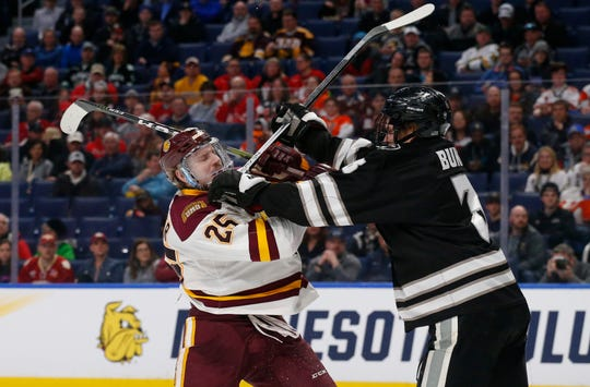 Minnesota-Duluth forward Peter Krieger (25) and Providence defenseman Davis Bunz (3) battle during the second period in a semifinal of the Frozen Four NCAA men's college hockey tournament Thursday, April 11, 2019, in Buffalo, N.Y. (AP Photo/Jeffrey T. Barnes)