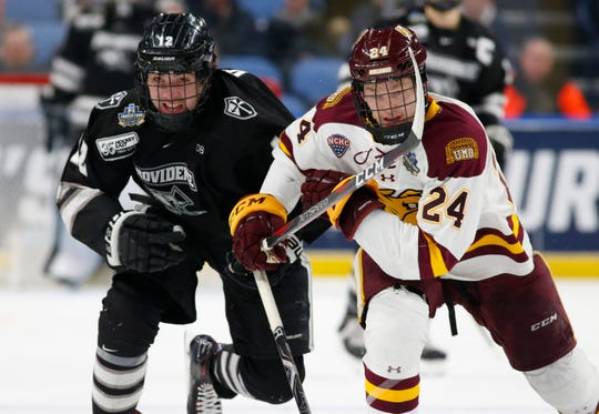Minnesota Duluth defenseman Mikey Anderson (24) and Providence forward Jack Dugan (12) of Rochester and McQuaid Jesuit skate during the first period in the semifinal of the Frozen Four NCAA college hockey tournament, Thursday, April 11, 2019, in Buffalo, N.Y. (AP Photo/Jeffrey T. Barnes)