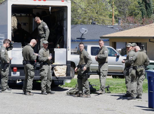 SWAT team members pack up after a gunman inside an Oxford Road home surrendered Friday.