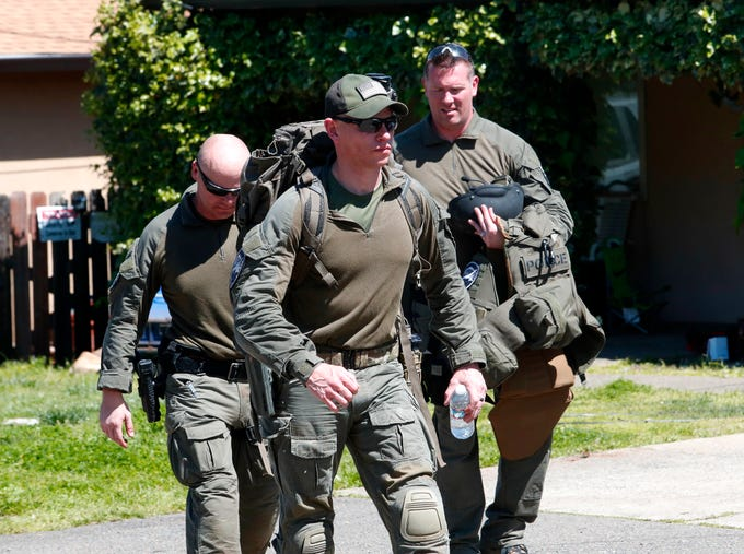 SWAT team members leave the scene of an eight-hour standoff after a man surrendered to them Friday in east Redding.