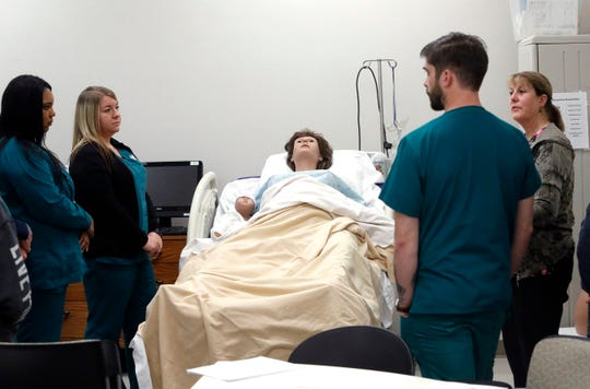 Vocational nursing instructor Nancy Skaggs, right, tells Shasta College students about a medical manikin they're about to practice on.