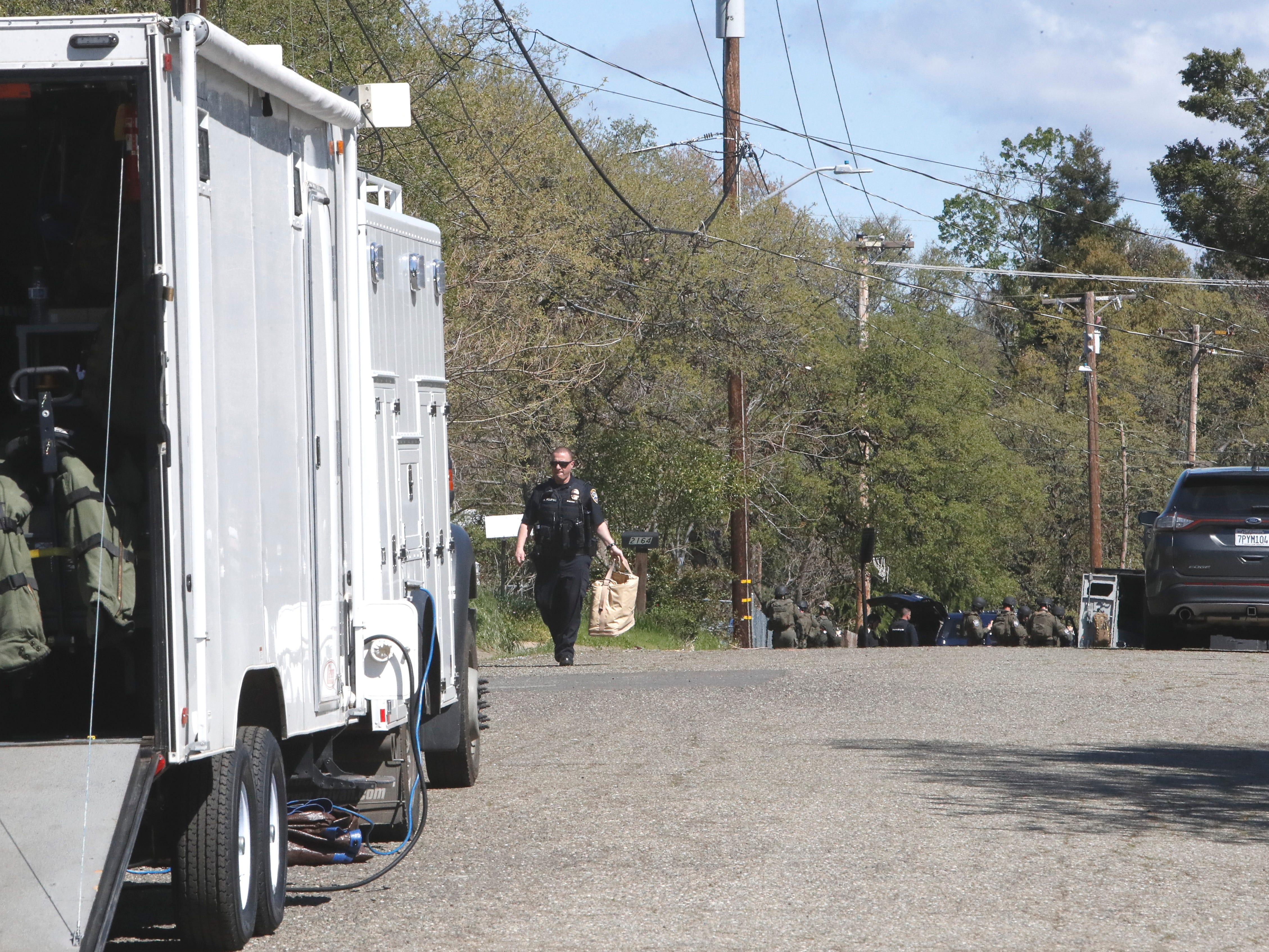 A SWAT team gathers outside a home on Oxford Road where a gunman was holed up for about eight hours Friday.
