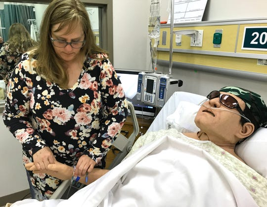 Lynnette Crowe takes the pulse of a medical manikin named Apollo at Shasta College's downtown health sciences facility. Crowe is the college's nursing clinical skills lab coordinator.