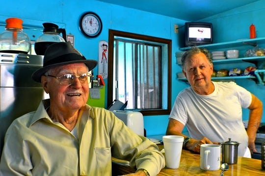 A customer sits with longtime Snack Shack owner Rich Barreau in this 2013 photo. Barreau died in late December.