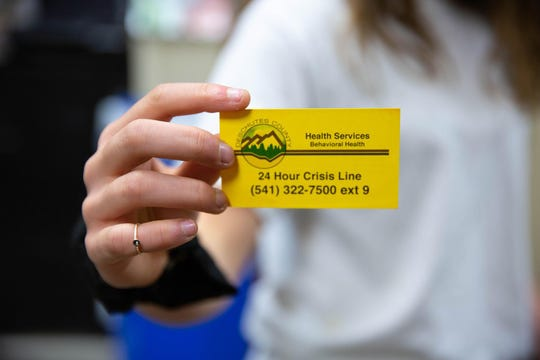 Sydney Wilkins holds a card for the 24-hour crisis line — she keeps it in her phone case.